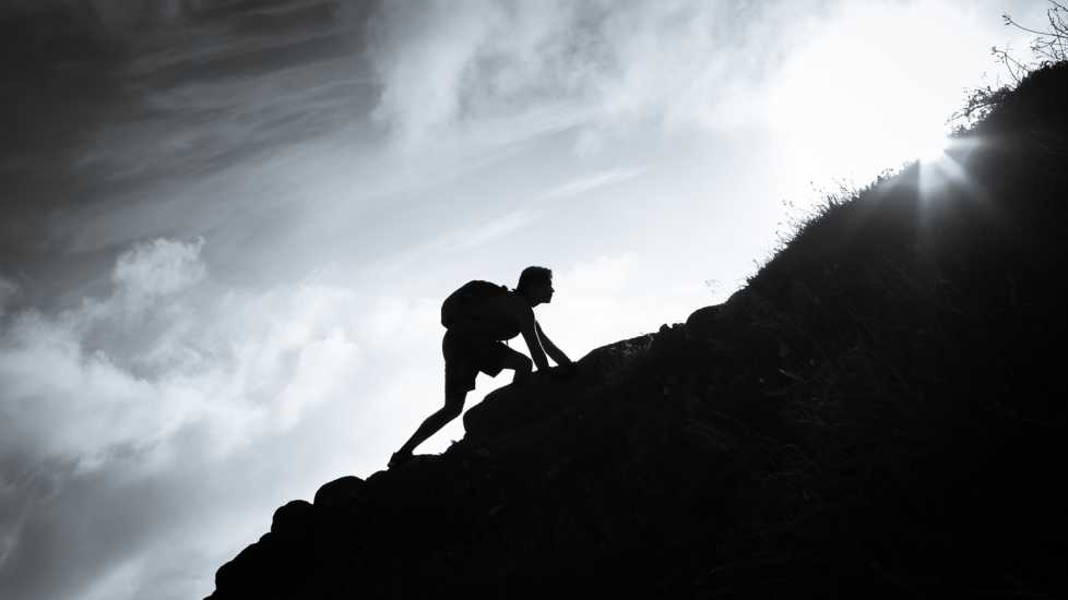 A silhouette of a person climbing up a large mountain.