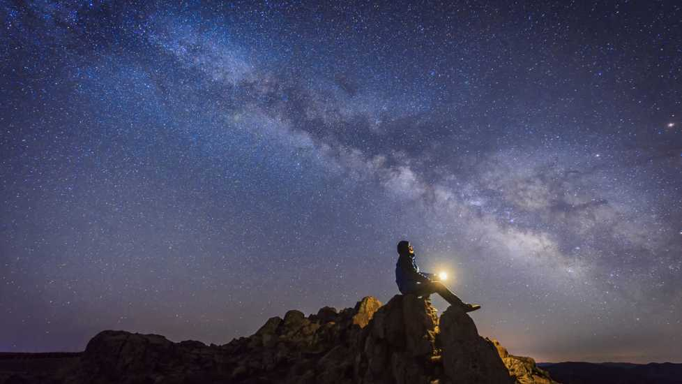 A man observing a starlit night.