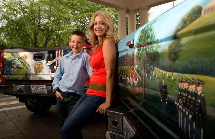Andrea and her son, Brayden, pose by the two tailgates she painted