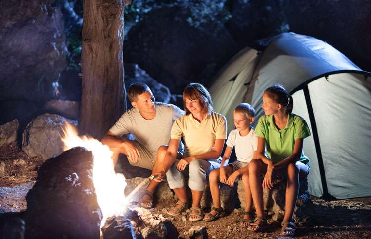 A family toasts marshmallows around a roaring campfire.