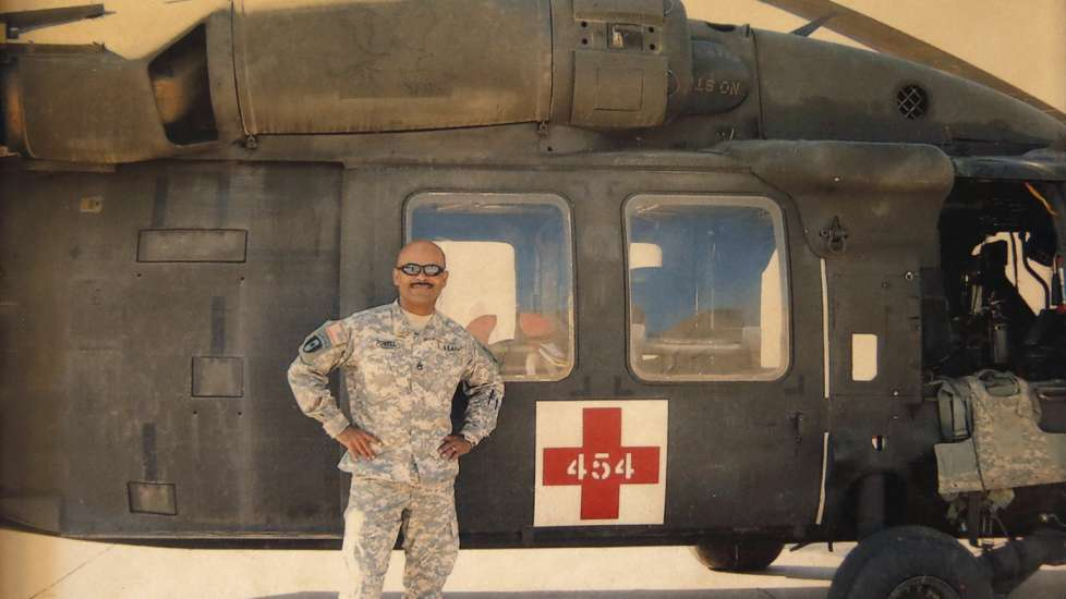 Powell stands with a U.S. Army MEDEVAC helicopter during his last tour in Iraq.