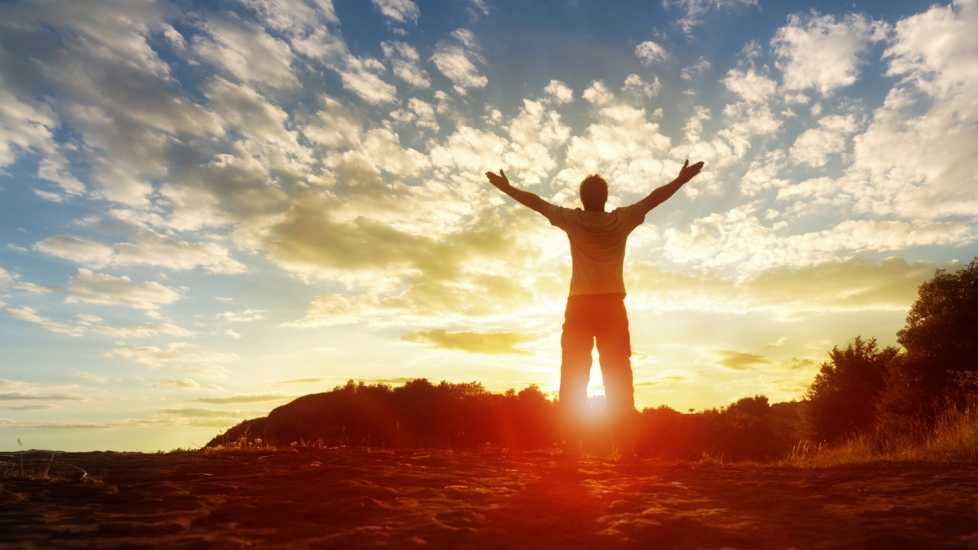 A person with arms outstretched towards the sky as daylight breaks.
