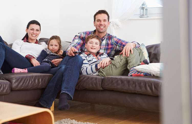 A family relaxes on the couch watching television together