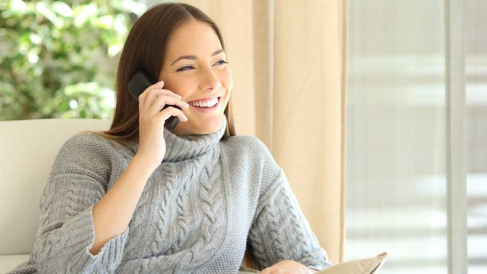A woman happily answering a phone call.