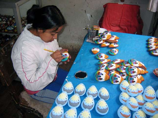 A young woman paints a traditional Peruvian instrument call the ocarina.