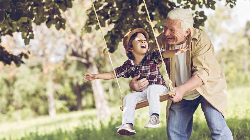 Retired grandfather pushing his grandson on a swing
