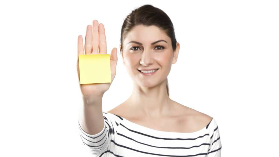 A woman with a post-it note on her hand.