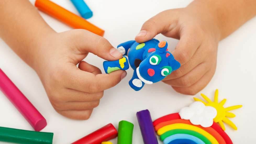 A child's hands building an animal with blue Play-Doh.