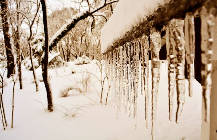 Guideposts: A line of lengthy icicles hang from the eave of a home