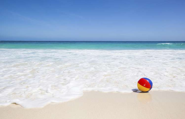 Guideposts: A beach ball floats on the incoming tide on a sunny beach
