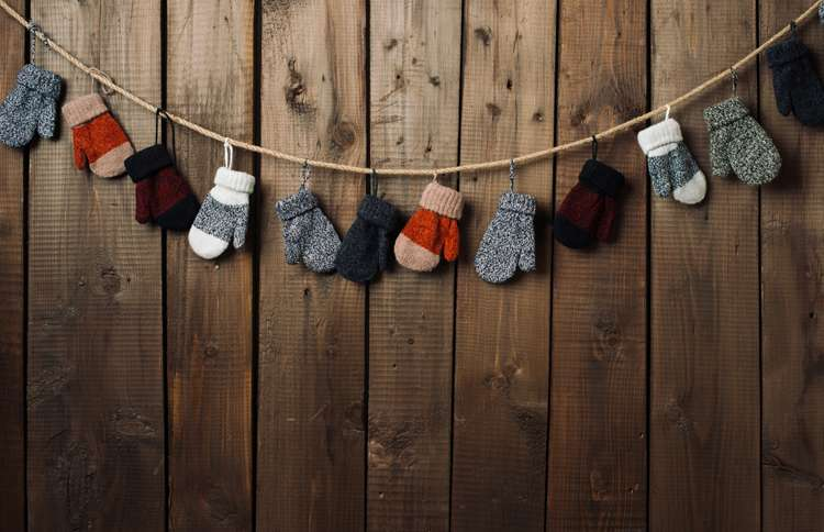 Guideposts: A collection of mittens are hung to dry along a wall