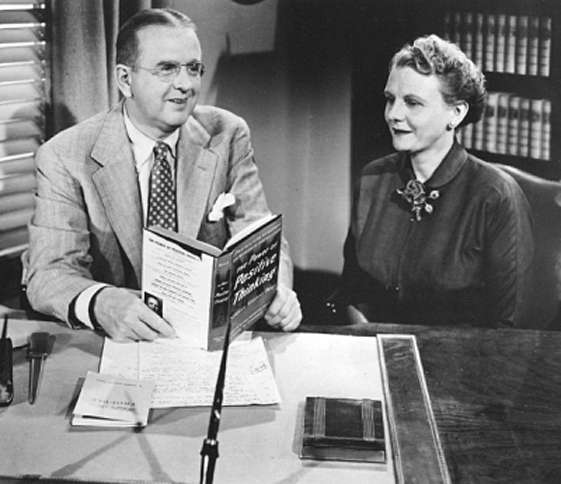 Dr. Norman Vincent Peale, with a copy of The Power of Positive Thinking in his hand and his wife, Ruth, at his side