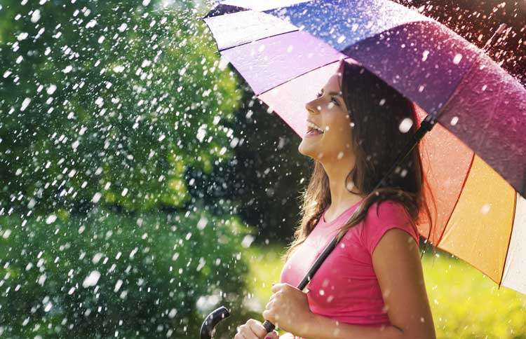 Guideposts: A smiling young woman with a brightly colored umbrella walks in the rain