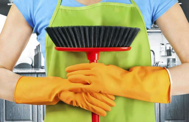 Guideposts: A woman's hand, wearing rubber gloves and clasping a broom