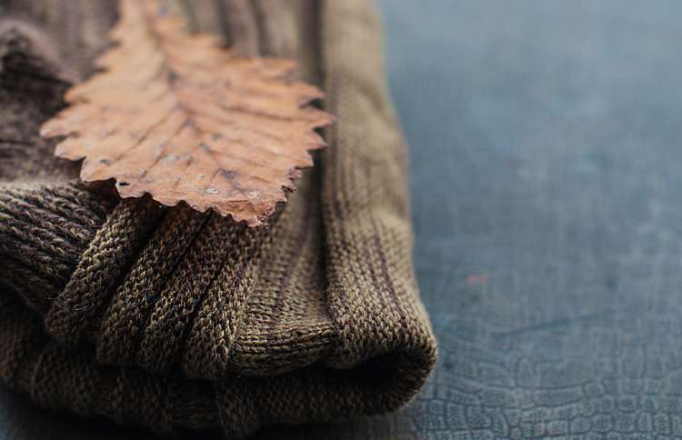 Guideposts: A folded woolen sweater on a shelf, with a single autumn leaf resting on it.