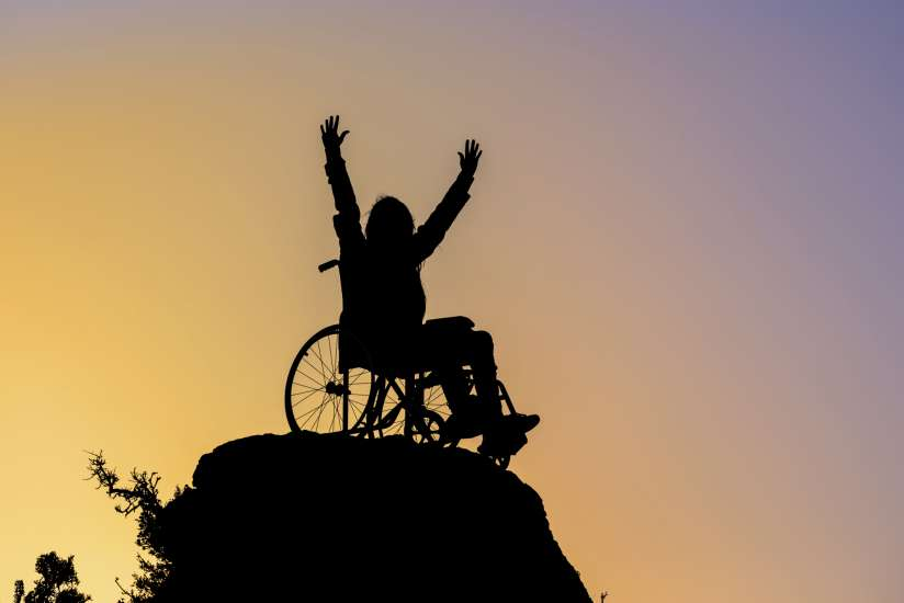 person in wheelchair at the top of a mountain at sunset