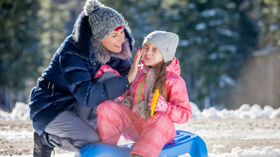 Health myths about Winter: Skip the Sunscreen. Mother applying sunscreen to daughter in winter. better living health wellness