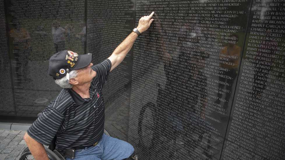 Eddie points to a name on the memorial wall