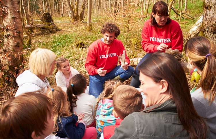 Guideposts: A pair of team leaders instruct a group of volunteers of all ages
