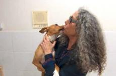Woman gives puppy a kiss.