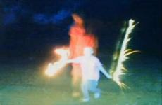 An evening shot of Erin playing with sparklers, and a figure standing nearby