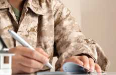 Guideposts: A soldier in camouflage fatigues writes out a check to pay a bill