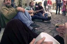 Three friends gather to perform music to raise money for a homeless man.