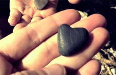 An outstretched hand holding a small rock shaped like a heart