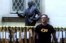 Mitch Horowitz poses with a statue of Norman Vincent Peale.