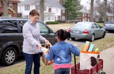 A little girl collecting food to be donated receives a contribution.