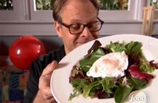 Alton Brown poses with a poached egg atop a green salad