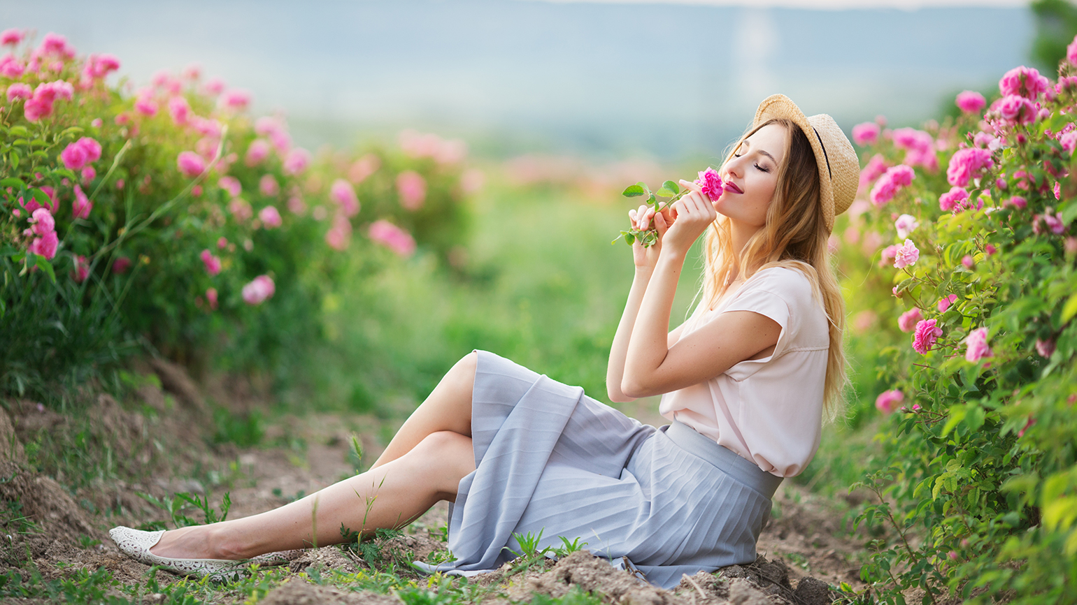 A woman stops to smell the roses on a warm summer day