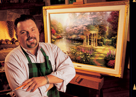 Thomas Kinkade with one of his paintings