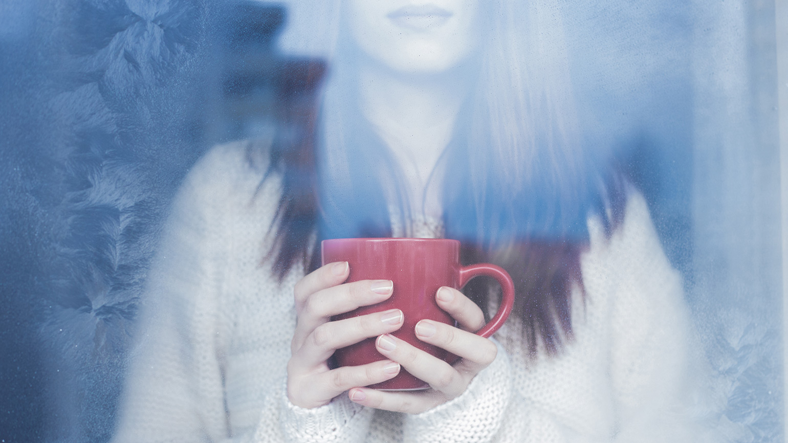 A woman gazes out a window, a warm cup of tea cradled in her hands