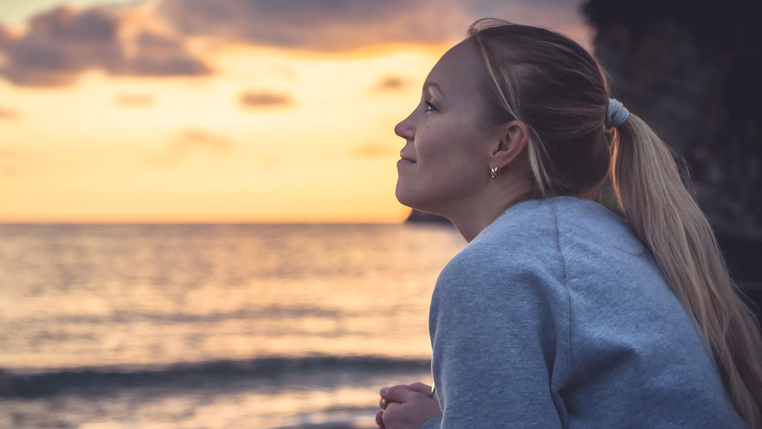 A contented woman looks out at a sunset over a beach