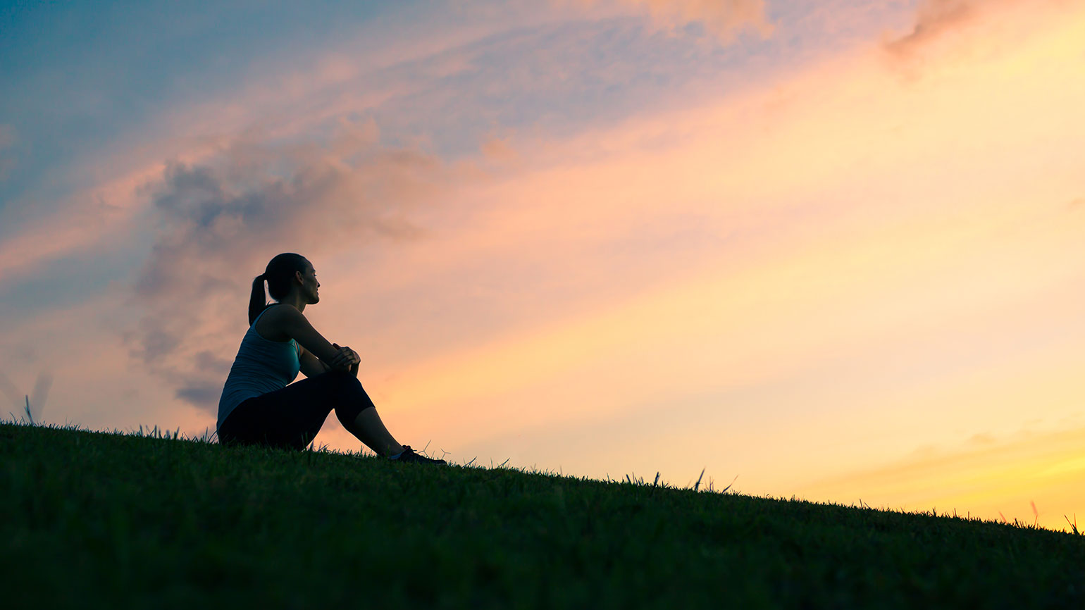 A woman enjoys a moment of peace and calm at sunrise