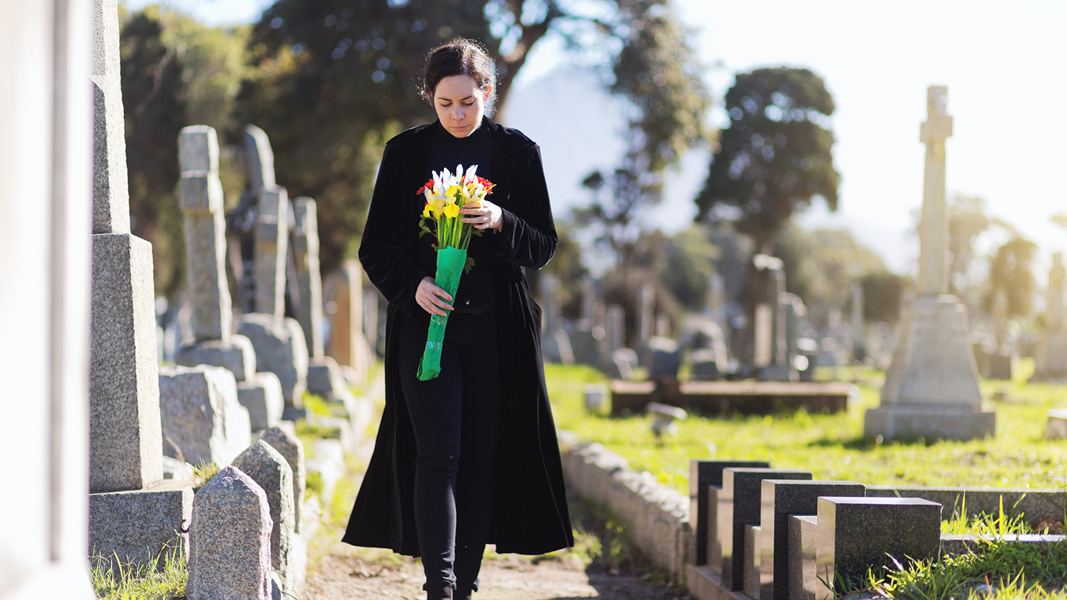 A grieving caregiver visits a cemetery