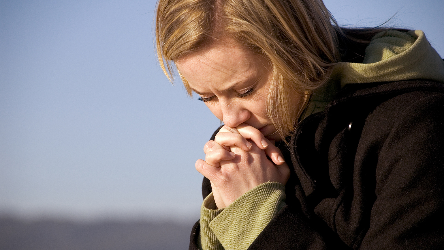 A woman bows her head in prayer
