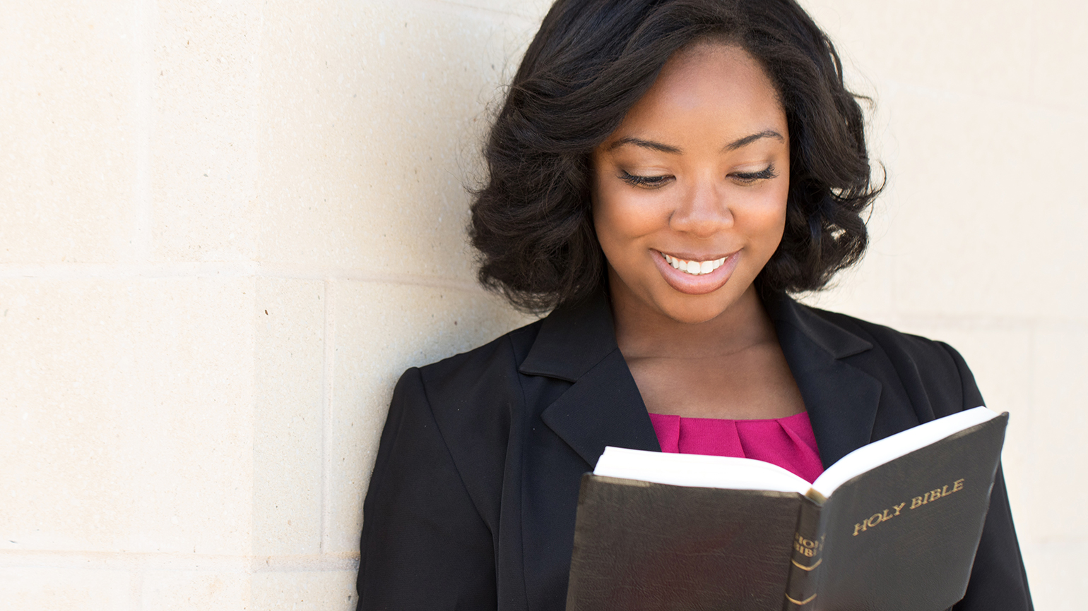 A smiling woman reads her Bible
