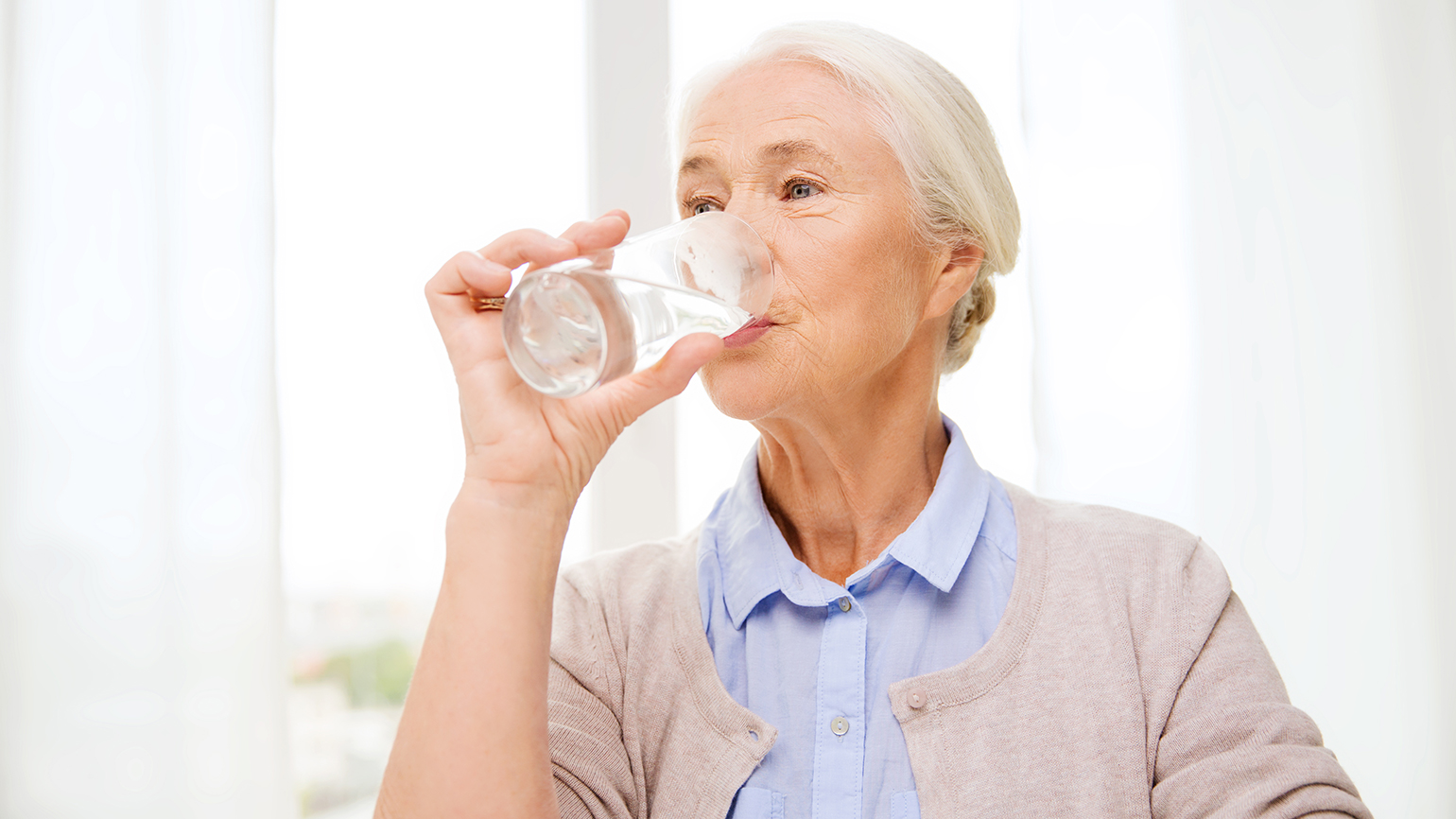 A senior woman drinks a tall glass of water