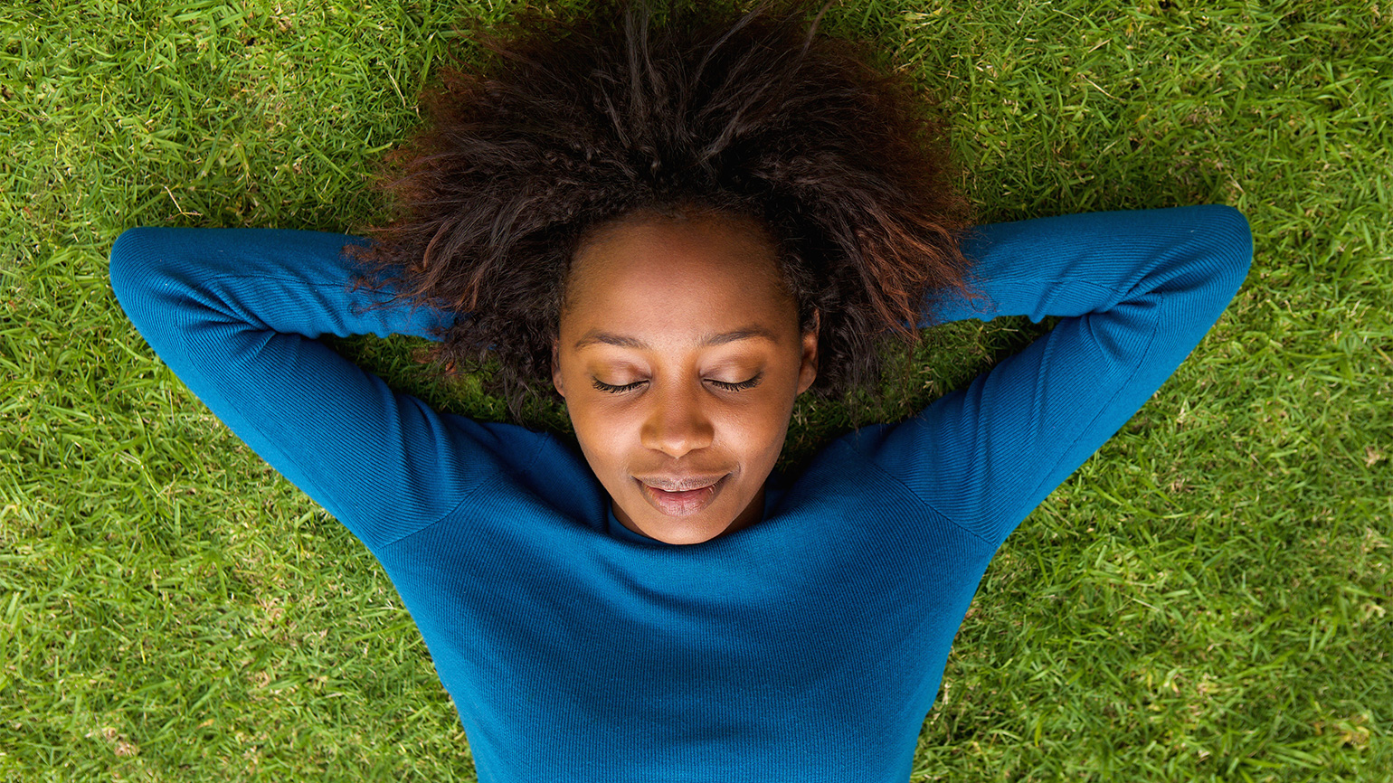 A woman rests on the green grass