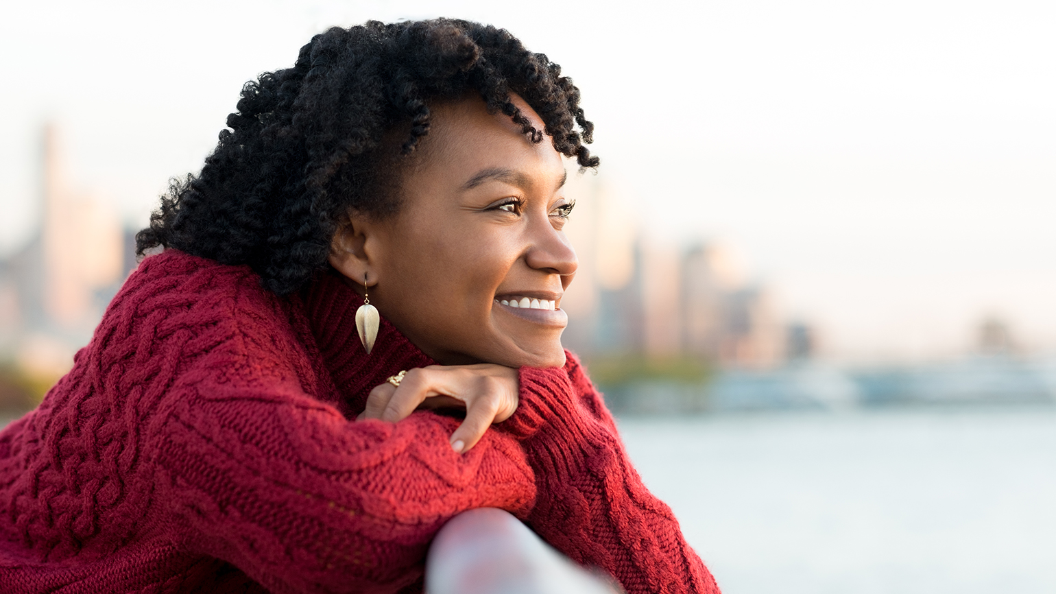 A smiling young woman stands on the banks of a river
