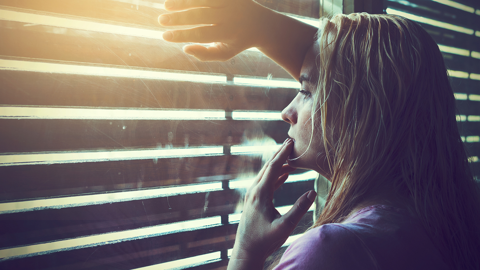 A grieving woman looks out her window through the blinds