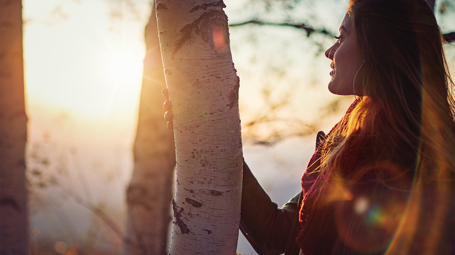 The morning sun shines on a woman in a forest