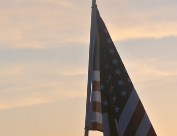 An American flag on a pole set against a sky at sunset
